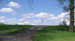 Bicycle path to river dike. Wheelchair cyclist passes. Stock Footage