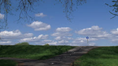 Touring cyclist over Dutch river dike - wide shot Stock Footage