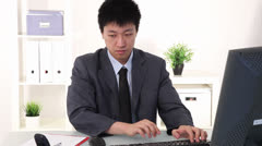 Young Asian businessman working at his desk Stock Footage