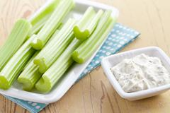 Green celery sticks with tasty dip Stock Photos