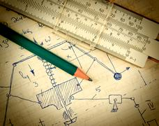 Pencil and a slide rule on the old page with the calculations in mechanics Stock Photos