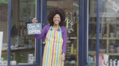 Happy female shopkeeper holds up a sign to show she is open for business Stock Footage