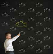 Writing boy dressed as business man with independent thinking chalk fish Stock Photos