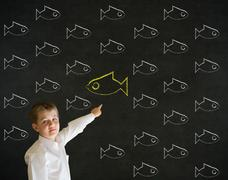 Pointing boy dressed as business man with independent thinking chalk fish Stock Photos