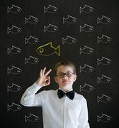 all ok boy dressed as business man with independent thinking chalk fish - stock photo
