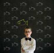 thinking boy dressed as business man with independent thinking chalk fish - stock photo