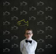 Thinking boy dressed as business man with independent thinking chalk fish Stock Photos