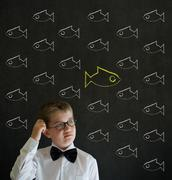 scratching head thinking boy dressed as business man with independent thinkin - stock photo