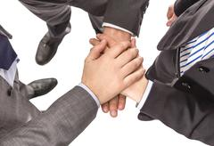 business partners with hands above showing power and unity - stock photo
