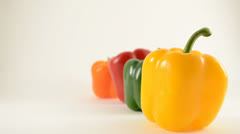 Yellow, Green, Red and Orange Peppers Against White - Crane Down Stock Footage