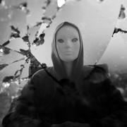 masked figure broken mirror - stock photo
