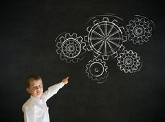 Pointing boy dressed as business man with chalk turning gear cogs or gears Stock Photos