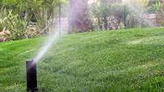 Garden irrigation sprikler watering lawn Stock Footage