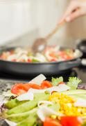closeup of fresh salad dish and female cooking in a pan - stock photo