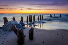 Stones and breakwater at sunset - stock photo