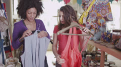 Two attractive women shopping together for new clothes Stock Footage