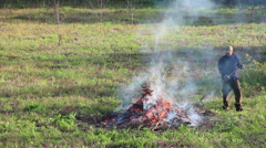 Fire on the field - man burning branches and brushwood 30fps Stock Footage