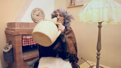 Grandma strange eagerly drinking from an earthenware jug Stock Footage