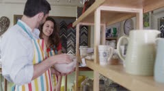 Two young store assistants chat together as they work - stock footage