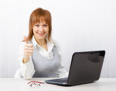 Attractive girl with a thumb up in the office Stock Photos