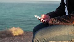 Close up of man`s hands using smartphone by the sea HD Stock Footage