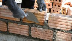 Labor build brick in construction site Stock Footage