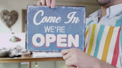 Happy businessman hangs an 'open' sign in the window of his shop Stock Footage