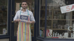 Happy business partners outside a shop hold up a sign to show they are open - stock footage