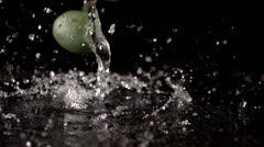 Citrus fruits drenched in water fall in slow motion against a black background - stock footage