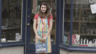 Stock Video Footage of Happy female shopkeeper holds up a sign to show she is open for business