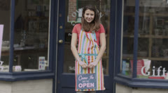 Happy female shopkeeper holds up a sign to show she is open for business - stock footage