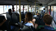 Bus passengers get up from their seats in order to get off at a busstop - stock footage