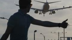 Man catches car on a background of landing airplane in Los Angeles Stock Footage