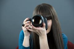 young woman with dslr over dark background - stock photo