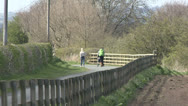 Women walk along country lane. Stock Footage