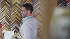 Two young sales assistants chatting and sharing a joke together as they work Stock Footage