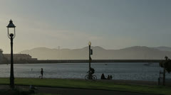 People walk in a park near the river in san francisco 2 Stock Footage