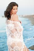 Portrait of a beautiful girl in a white shawl on the beach. - stock photo