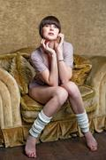 Girl posing sitting on a chair. - stock photo