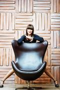 Girl model posing for a leather armchair. - stock photo