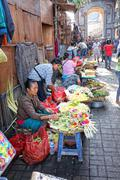 Balinese woman in market sell flower petals for everyday offering Stock Photos