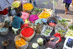 Balinese woman in market sell flower petals and fruits for everyday offering Stock Photos