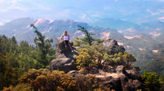 Attractive woman on a rocky hilltop takes in the spectacular views around her Stock Footage
