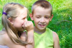 Little girl whispering something to her brother Stock Photos