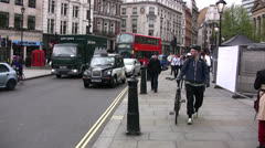 Busy road in Trafalgar square with black taxis and pedestrians Stock Footage