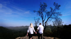 Romantic couple on vacation walk hand in hand and take in the spectacular views Stock Footage