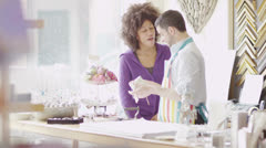 Two sales assistants or business partners chat together as they work Stock Footage