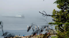 Ferry emerging from Fog / People on Beach Stock Footage