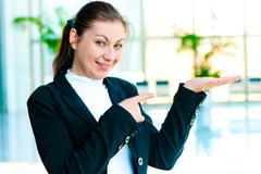 Happy young woman holding something on the palm of your hand and points a finger Stock Photos