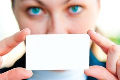 A girl showing a blank business card - stock photo